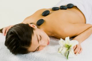Portrait of young woman at the day spa with black stones on her bare back